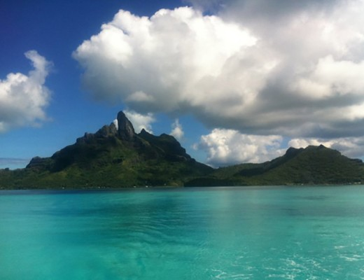 Turquoise ocean with island and clouds